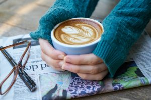 latte in hands with turquoise sweater